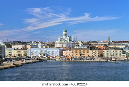 Helsinki, Finland. Scenic cityscape with Helsinki Cathedral, South Harbor, Market Square (Kauppatori) and beautiful cirrus clouds over them in the sunny spring day.