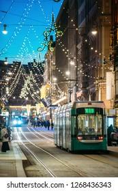 Helsinki, Finland. Tram Departs From Stop On Aleksanterinkatu Street. Night Evening Christmas Xmas New Year Festive Street Illumination. Beautiful Decorations During Winter Holidays