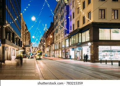 Helsinki, Finland. Tram Departs From Stop On Aleksanterinkatu Street. Street With Railroad In Kluuvi District In Evening Or Night Christmas Xmas New Year Festive Illumination