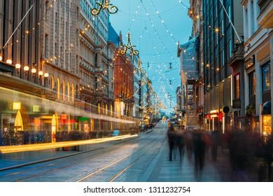 Helsinki, Finland. Trams Departs From Stop On Aleksanterinkatu Street. Night Evening Christmas Xmas New Year Festive Street Illumination. Decorations During Winter Holidays