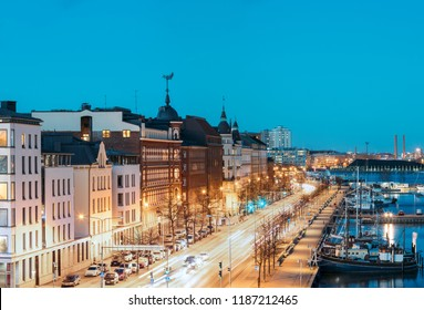 Helsinki, Finland. View Of Pohjoisranta Street And Ships, Boats And Yachts Moored Near Pier In Evening Night Illuminations.