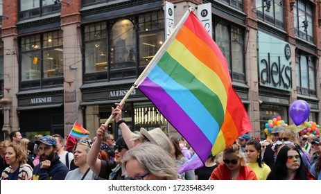 Helsinki Pride photographed in Helsinki, Finland, June 2019. People marching for equal rights for LGBT community with rainbow flags and colorful signs. Color image of the parade symboling equality.