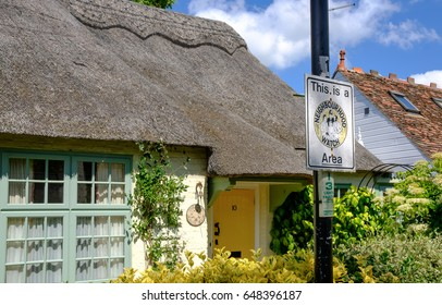HEMMING FORD ABBOTS, CAMBRIDGESHIRE, UK - CIRCA MAY 2017: Quintessential view of a typical English thatched cottage in early summer. Also seen is a metal sign of a neighboured watch scheme running.