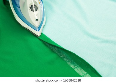 Hemming, shortening a green courtain fabric with an iron and the iron-on adhesive hemming tape - quick way to fix fabrics and clothes with no sewing - Shutterstock ID 1653842518
