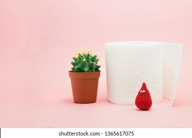 Hemorrhoid, constipation treatment health problems. Toilet paper, a cactus and crochet blood drop on the pink background. Hemorrhoid problems