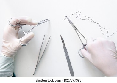 Hemostatic forceps and needle holder were used for surgical suture under the white background