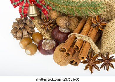Hemp bag with cinnamon, star anise, walnuts, chestnuts, red bow with bell and fir branches on a white background close-up