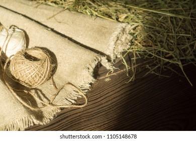 Hemp canvas and threads on a dark wooden surface
