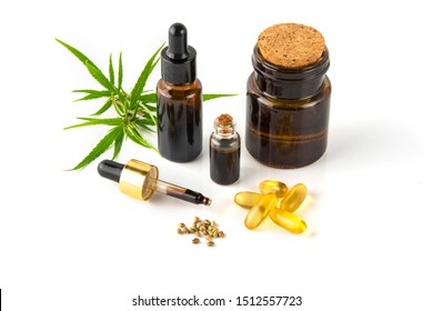 hemp essential oil in small glass bottle. container with cannabis leaves and cannabis seeds on white background.