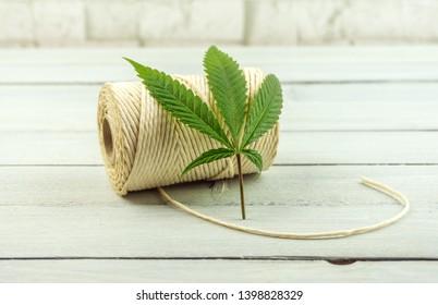Hemp fiber rope twine and Hemp leaf on bright wooden table