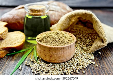 Hemp flour in a bowl, seed in a bag on the table, oil in a glass jar,  cannabis leaf and bread on a wooden boards background