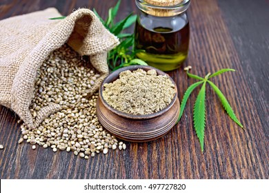 Hemp flour in a clay bowl, the grain in the bag and on the table, the oil in a glass jar, leaves and stalks of cannabis on a background of dark wooden boards