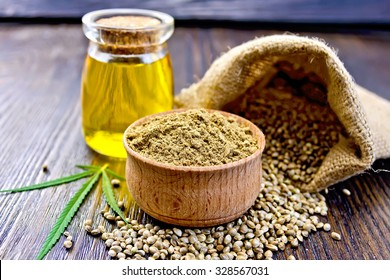 Hemp Flour in a wooden bowl, seed in a bag and on the table, oil in a glass jar, cannabis leaf on the background of wooden boards