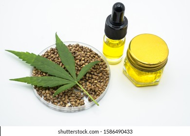 Hemp leaves are placed on seeds and CBD oil bottles. White background The concept of medical marijuana in the treatment of diseases has.The cycle of marijuana used is refined CBD hemp oil.