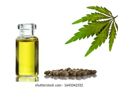 Hemp oil in a glass vial with cannabis seeds and a marijuana leaf. Isolated on white background.