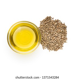 Hemp oil and pile of hemp seeds isolated on white background, top view. Pure cold pressed oils concept
