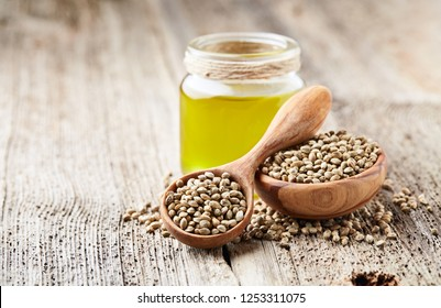 Hemp oil and seeds on wooden background