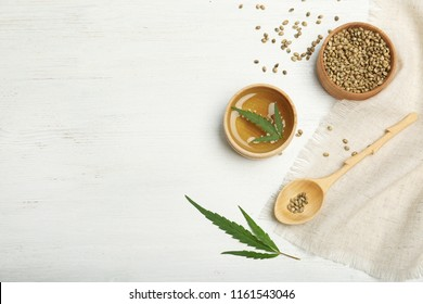 Hemp oil, seeds and space for text on white wooden background, flat lay