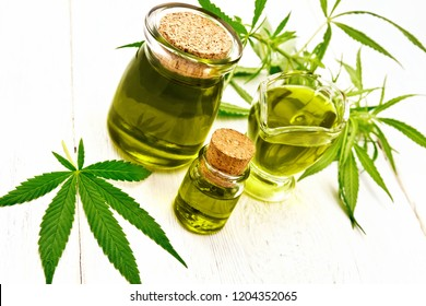 Hemp oil in two glass jars and sauceboat, leaves and stalks of cannabis on the background of wooden boards