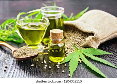 Hemp oil in two glass jars and sauceboat with grain in the bag, leaves and stalks of cannabis, a spoon with flour on the background of wooden boards