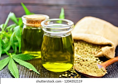 Hemp oil in two glass jars, grain in a bag and on the table, flour in a spoon, cannabis leaves against a dark wooden board