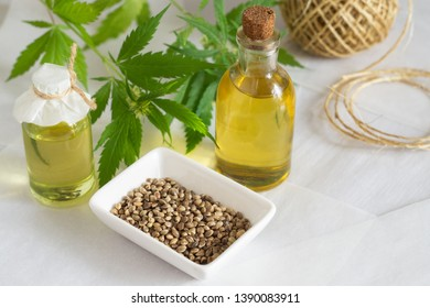 Hemp products concept. Bottles with cannabis oil, a skein of thread and a green plant on a white background