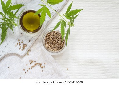 Hemp products concept. Seeds, cannabis oil and green plant on white homespun cloth