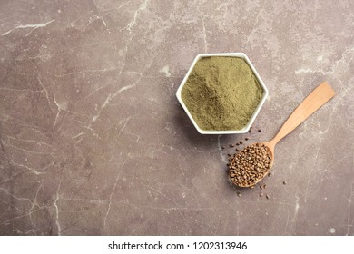 Hemp protein powder in bowl and spoon with seeds on table, top view. Space for text