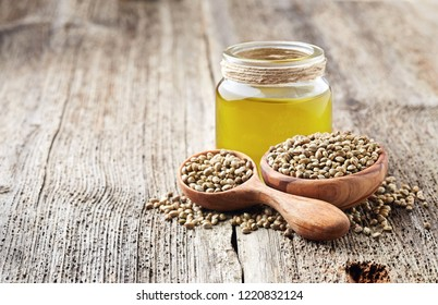 Hemp raw oil and seeds on wooden board