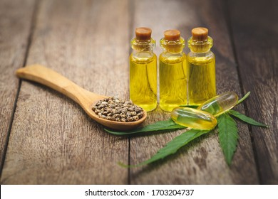 Hemp seeds and hemp oil on brown wooden table. Hemp seeds in wooden spoon and hemp essential oil in small glass bottle.
