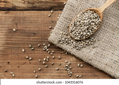 hemp seeds in a rustic wooden spoon on the burlap napkin, space for text