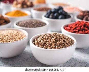 Hemp seeds in small white bowl and other superfoods on background. Selective focus. Different superfoods ingredients. Concept and illustration for superfood and detox food