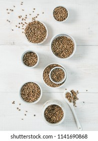 Hemp seeds in small white bowls and spoon on white wooden table. Set of small bowls with raw organic unrefined hemp seed. Superfood and vegan concept. Top view or flat lay.Copy space for text.Vertical