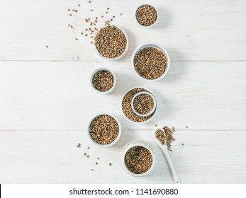 Hemp seeds in small white bowls and spoon on white wooden table. Set of small bowls with raw organic unrefined hemp seed. Superfood and vegan concept. Top view or flat lay.Copy space for text