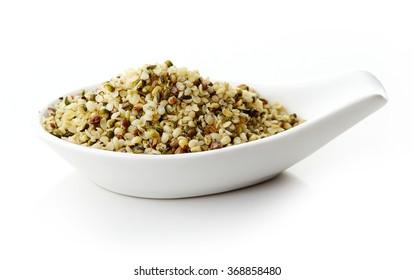 Hemp seeds in white porcelain spoon on white background