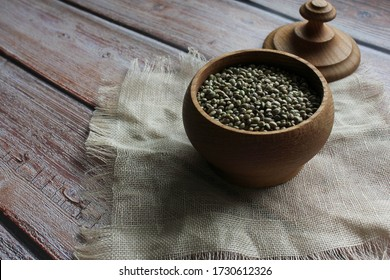 Hemp seeds in a wooden container. Close up. Copy space.