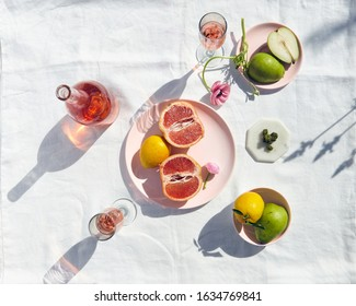 Hemp/Cannabis Flower still-life with Rose`, grapefruit, pears, and lemons on pink plates and white linen tablecloth.