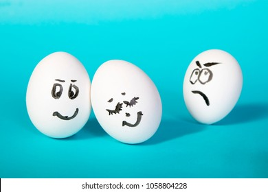 hen eggs with painted faces. The dissatisfied man looks at the happy couple. Jealousy. Blue background.