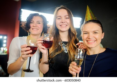 Hen night on the eve of the wedding. Girlfriends have fun. Stemware with champagne. Congratulations. Elegantly dressed girls spend time on a hen night with pleasure. Cheerful party