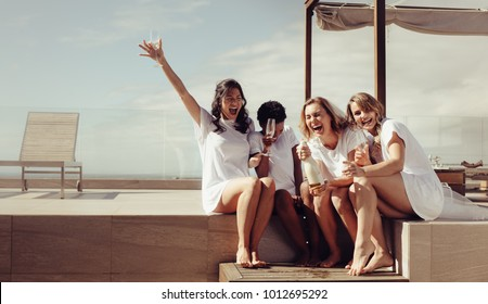 Hen party on the rooftop. Bride and bridesmaids having champagne and laughing. Girls are going crazy before wedding.