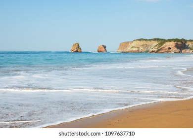 Hendaye sandy beach landscape with beautiful twin huge rocks at background. Nouvelle-Aquitaine, France.