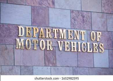 "Henderson, NV 2/22/2020 — ""Department of motor vehicles"" written in gold font on brick wall of a full service DMV Nevada location in a suburban city of Las Vegas."