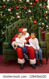 Henderson, NV, USA - Dec 06-2018 - Santa Claus with kids in front of a Christmas tree at the shopping mall Galleria at Sunset, Las Vegas.