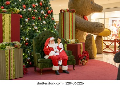 Henderson, NV, USA - Dec 06-2018 - Santa Claus with a girl on his knee in front of a Christmas tree at the shopping mall Galleria at Sunset, Las Vegas.