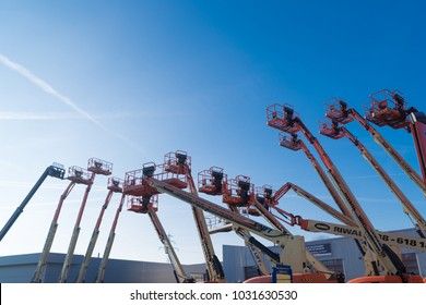 HENGELO, NETHERLANDS - JANUARY 21, 2017: Various mobile scissor lift platforms for rent against a blue sky