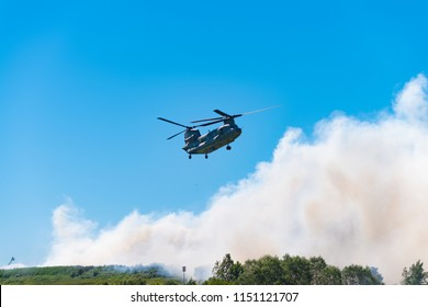 HENGELO, NETHERLANDS - JULY 1, 2018: Dutch Chinook army helicopter extinguishes a large fire at a local waste processing company during a hot summer