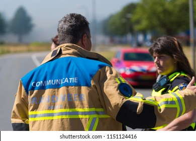 HENGELO, NETHERLANDS - JULY 1, 2018: Unknown fire department communication (brandweer communicatie in dutch language) officer explaining the situation to a police officer
