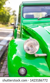 Hengelo / Netherlands - June 11 2019 : Closeup on one side of the front of a bright green car, a Citroën 2CV, on a sunny day