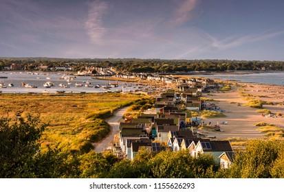 Hengistbury Head  beach huts in Bournemouth under a golden evening sun