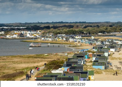 Hengistbury Head,Bournemouth, UK, March 17th 2019; Busy scene of Colourful painted  beach huts at Christchurch harbour  with sandy beaches and beautiful sky.